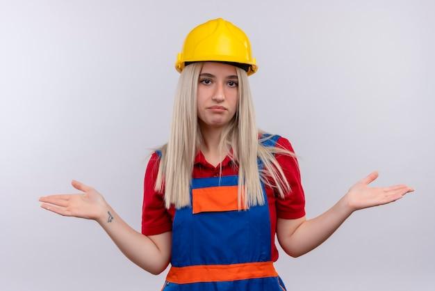 Смущенная молодая блондинка инженер-строитель девушка в униформе показывает пустые руки на изолированном белом пространстве