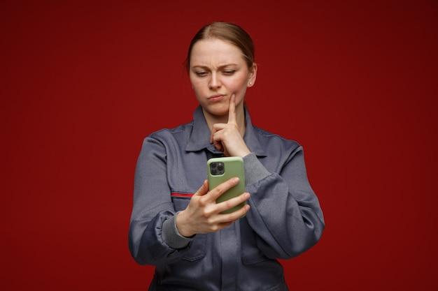 Confuso giovane bionda ingegnere femminile che indossa uniforme che tiene e guardando il telefono cellulare toccando il viso con il dito