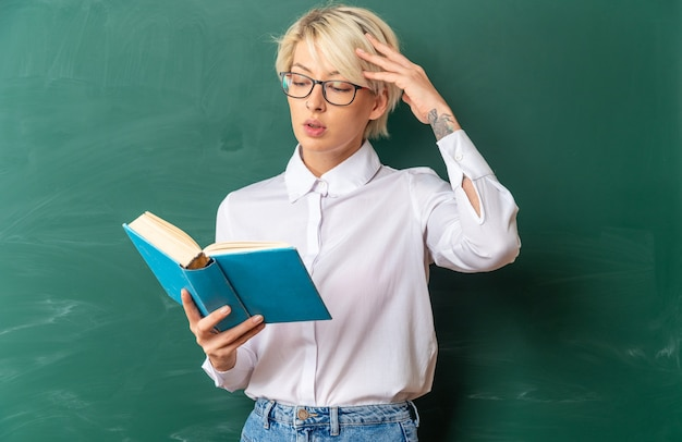 頭に触れて本を持って読んで黒板の前に立っている教室で眼鏡をかけている混乱した若いブロンドの女性教師
