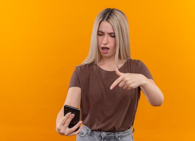 Giovane ragazza bionda confusa che tiene il telefono cellulare che indica e che lo esamina sullo spazio arancione isolato con lo spazio della copia