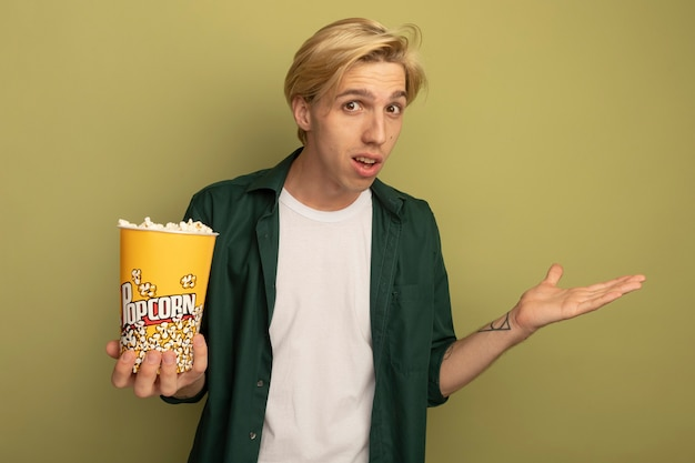 Confused young blonde guy wearing green t-shirt holding bucket of popcorn and spreading hand