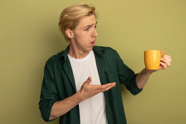 Confused young blonde guy wearing green t-shirt holding and points with hand at cup of tea