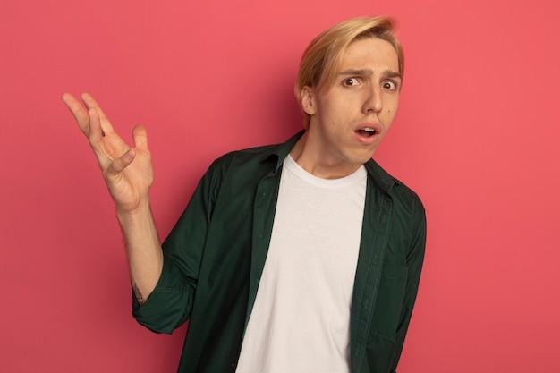 Giovane ragazzo biondo confuso che porta la mano di diffusione della maglietta verde