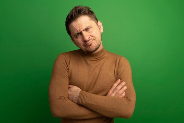 Confuso giovane biondo bell'uomo in piedi con la postura chiusa che sembra isolato sulla parete verde con spazio di copia