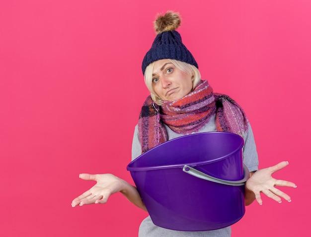 겨울 모자와 스카프를 착용하는 혼란 스 러 워 젊은 금발의 아픈 슬라브 여자 복사 공간이 분홍색 벽에 절연 플라스틱 양동이 보유
