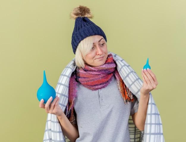 격자 무늬에 싸여 겨울 모자와 스카프를 착용하는 혼란 스 러 워 젊은 금발의 아픈 슬라브 여자 보유 및 복사 공간 올리브 녹색 벽에 고립 된 관장을 본다