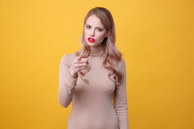 Confused young blonde lady with bright makeup lips pointing