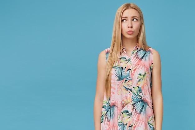 꽃이 만발한 셔츠를 입고 혼란스러운 젊은 금발의 긴 머리 아가씨, 손으로 포즈를 취하고 입술을 옆으로보고