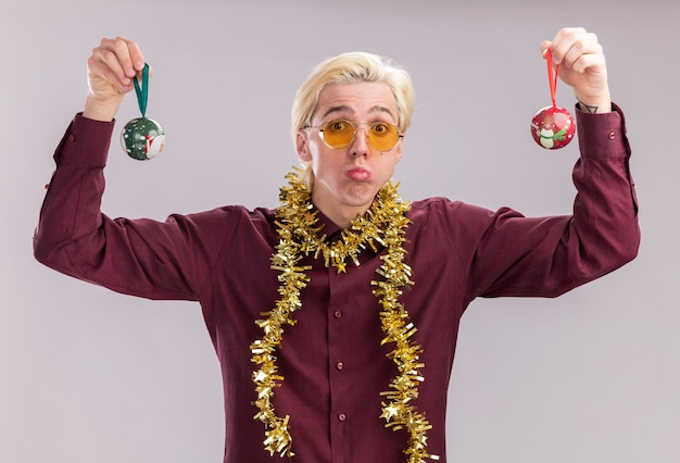 Confused young blonde man wearing glasses with tinsel garland around neck raising christmas baubles up looking at camera isolated on white background