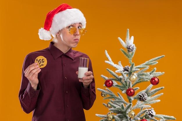 Confuso giovane uomo biondo che indossa santa cappello e occhiali in piedi vicino all'albero di natale decorato tenendo un bicchiere di latte e cookie guardando la telecamera isolata su sfondo arancione