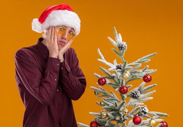 Confuso giovane uomo biondo che indossa santa cappello e occhiali in piedi vicino all'albero di natale decorato su sfondo arancione