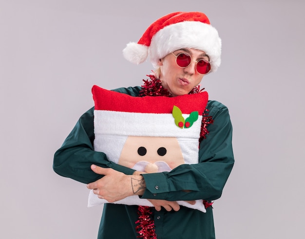 Confused young blonde man wearing santa hat and glasses with tinsel garland around neck hugging santa claus pillow looking at camera isolated on white background
