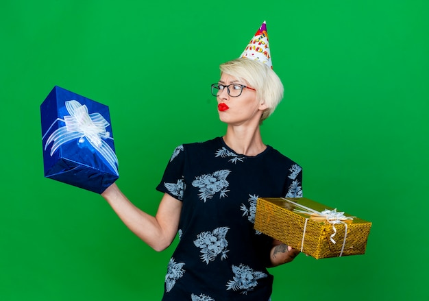 Confused young blonde party girl wearing glasses and birthday cap holding gift boxes looking at one of them isolated on green background