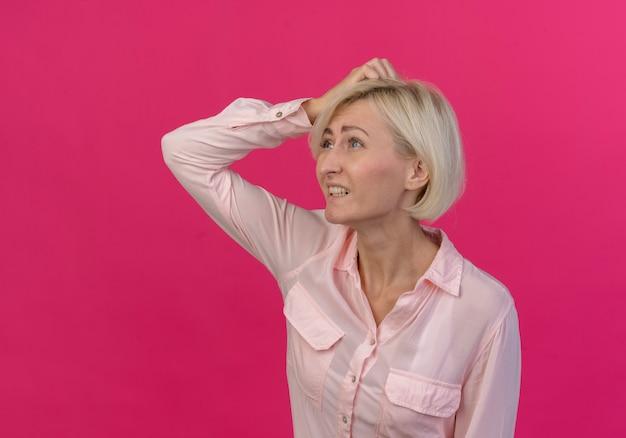 横を見て、コピースペースとピンクの背景で隔離の頭に手を置く混乱した若い金髪のスラブ女性
