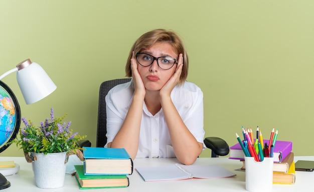 Confuso giovane studentessa bionda con gli occhiali seduto alla scrivania con gli strumenti della scuola che tiene le mani sul viso guardando la telecamera isolata sul muro verde oliva