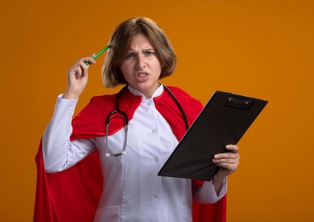 医者の制服と聴診器を身に着けている赤いマントの混乱した若い金髪のスーパーヒーローの女性はクリップボードを保持し、オレンジ色の壁に分離された正面を見て鉛筆で頭に触れます