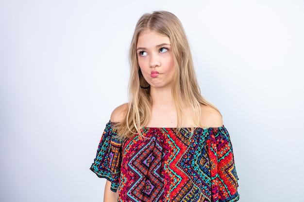 Confuso giovane donna bionda guardando a lato