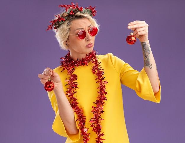 クリスマスの頭の花輪と首の周りに見掛け倒しの花輪を身に着けている混乱した若いブロンドの女性は、紫色の背景に分離されたそれらの1つを見てクリスマスつまらないものを保持している眼鏡