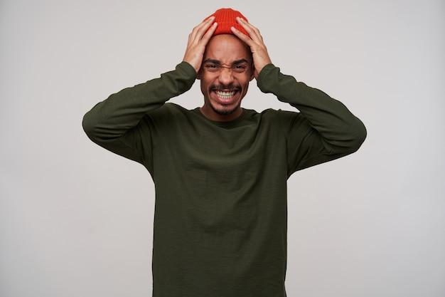 Confuso giovane ragazzo bruna dalla pelle scura barbuto dagli occhi marroni che aggrotta la fronte e tiene la testa con le mani alzate mentre, isolato su bianco