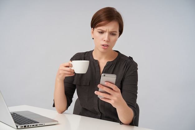 Confusa giovane signora dai capelli castani con taglio di capelli corto alla moda che aggrotta le sopracciglia mentre guarda lo schermo del suo telefono cellulare, tenendo la tazza di tè mentre posa su bianco