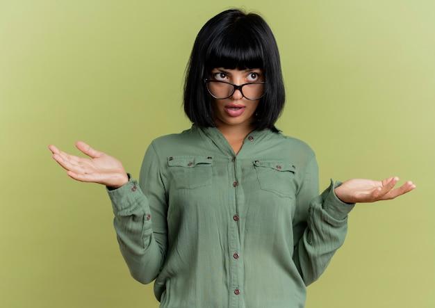 Confusa giovane ragazza caucasica bruna in vetri ottici tiene le mani aperte guardando il lato isolato su sfondo verde oliva con lo spazio della copia