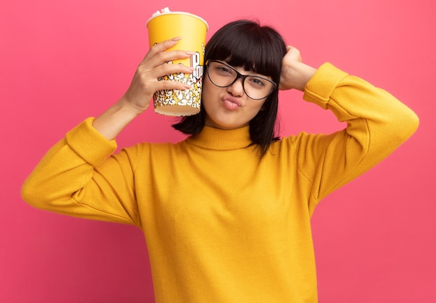 Confused young brunette caucasian girl in optical glasses puts hand on head and holds popcorn bucket isolated on pink wall with copy space