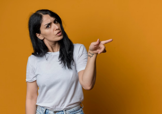 Confused young brunette caucasian girl points at side looking isolated on orange wall