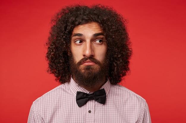 Смущенный молодой кудрявый мужчина брюнетки с бородой морщит лоб, глядя в сторону и скручивает рот, стоя в элегантной одежде