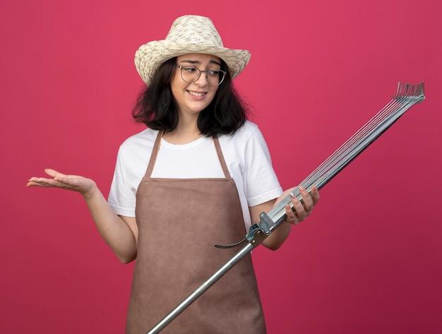 광학 안경과 원예 모자를 쓰고 제복을 입은 젊은 갈색 머리 여성 정원사를 혼란스럽게하고 복사 공간이 분홍색 벽에 고립 된 잎 갈퀴를 본다.