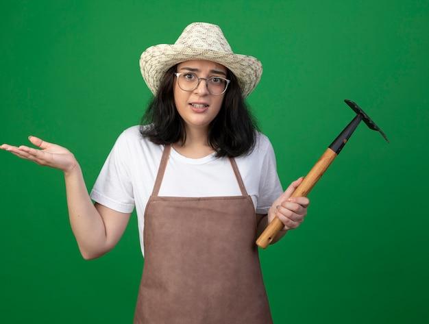 光学ガラスと制服を着た若いブルネットの女性の庭師は、上げられた手で立って、緑の壁に分離された熊手を保持します