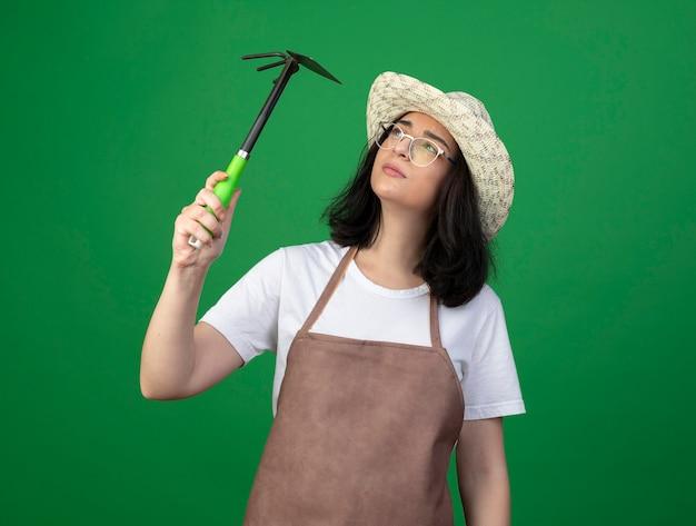 Giardiniere femminile giovane brunetta confuso in vetri ottici e cappello da giardinaggio da portare uniforme tiene ed esamina il rastrello della zappa isolato sulla parete verde