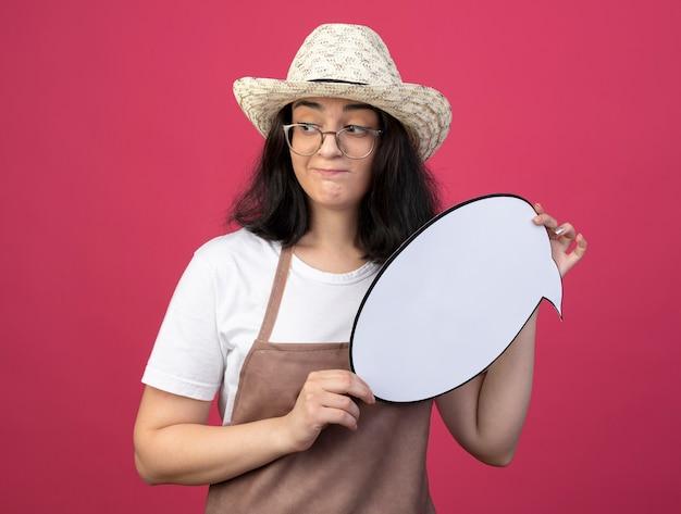 Giardiniere femminile giovane brunetta confuso in occhiali ottici e in uniforme che indossa il cappello da giardinaggio tiene il fumetto e guarda al lato isolato sul muro rosa