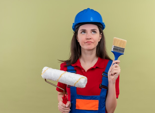 Confused young builder girl with blue safety helmet holds paint roller and paint brush on isolated green background with copy space