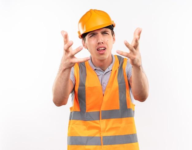 Confuso giovane costruttore in uniforme che porge le mani isolate sul muro bianco