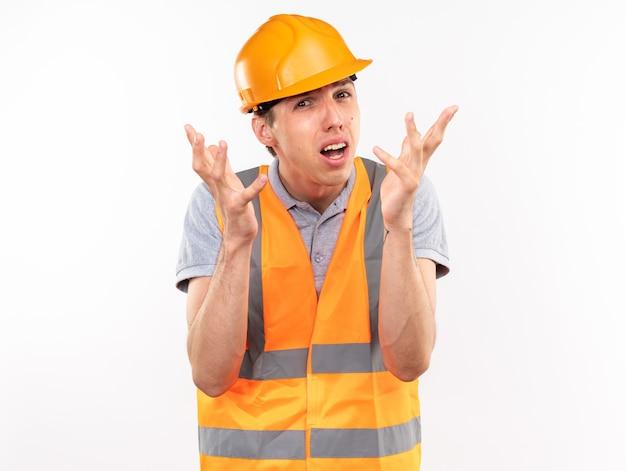 Confuso giovane costruttore in uniforme che spande le mani isolate sul muro bianco