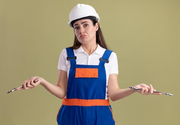 Donna confusa del giovane costruttore in uniforme che tiene le chiavi aperte che diffondono le mani isolate sulla parete verde oliva