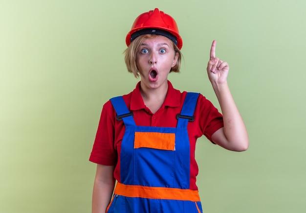 Confuso giovane donna costruttore in uniforme punta verso l'alto isolato sul muro verde oliva