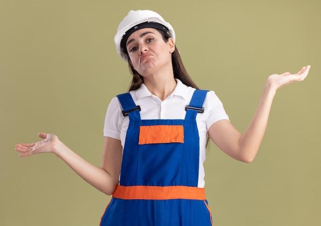 Giovane donna confusa del costruttore in uniforme che spande le mani isolate sulla parete verde oliva