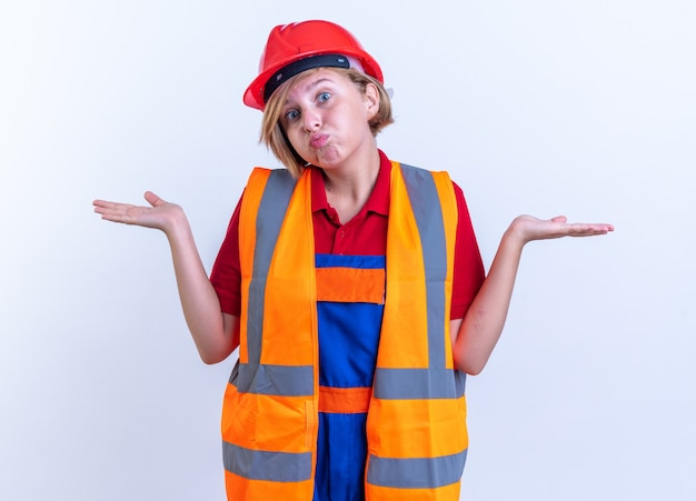 Confuso giovane donna costruttore in uniforme allargando le mani isolate sul muro bianco