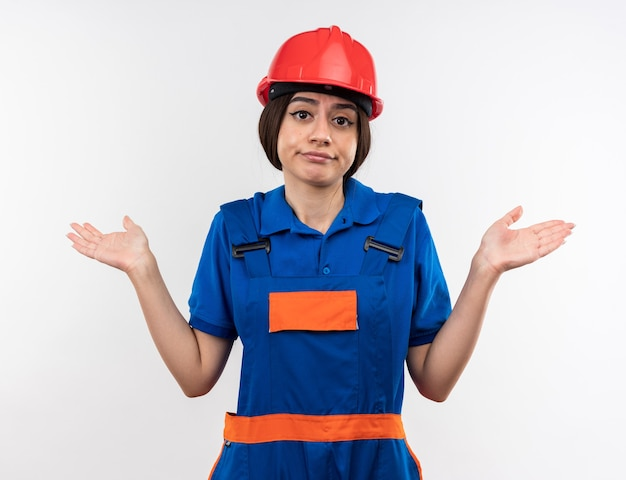Confused  young builder woman in uniform spreading hands isolated on white wall