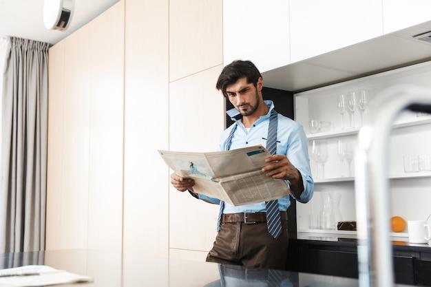 新聞を持っている台所で混乱した若いビジネスマン。