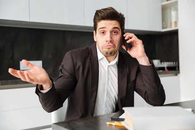 Confused young businessman talking by mobile phone.