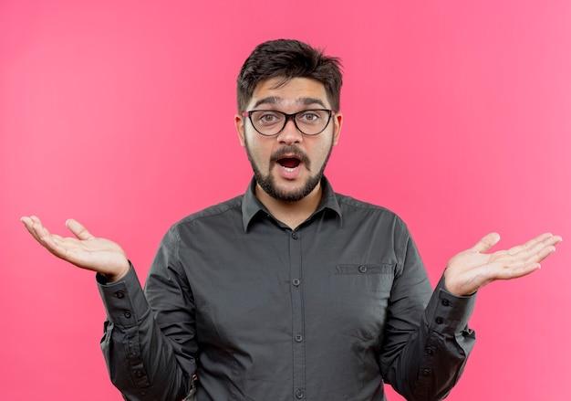 Смущенный молодой бизнесмен в очках разводит руками, изолированными на розовой стене