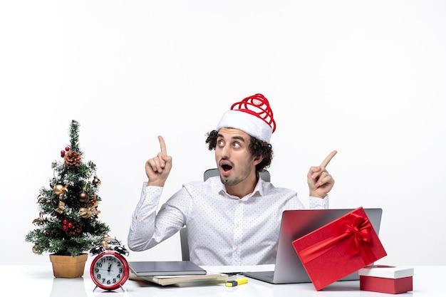 Confuso giovane imprenditore con buffo cappello di babbo natale che punta qualcosa in direzioni diverse in ufficio su sfondo bianco