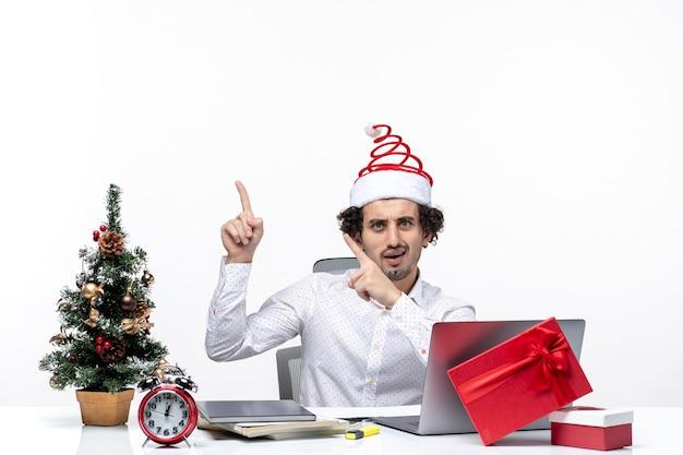 白い背景の上のオフィスの左側に何かを指している面白いサンタクロースの帽子で混乱した青年実業家