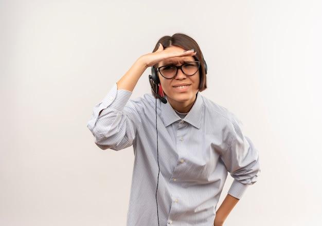 眼鏡とヘッドセットを身に着けている混乱した若いコールセンターの女の子は、コピースペースで白で隔離された距離を見て額の近くに手を保ちます