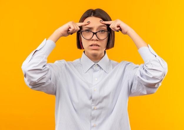 オレンジ色に分離された額に指を置く眼鏡をかけている混乱した若いコールセンターの女の子