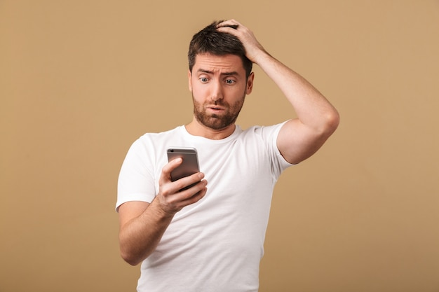 Confused young casual man holding mobile phone isolated