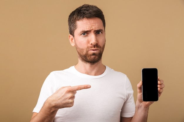 Confused young casual man showing blank screen mobile phone isolated