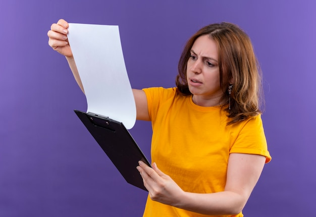 Confused young casual woman holding clipboard and looking at it on isolated purple space
